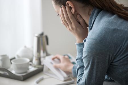 슬픈 우울한 여자 집에서 소파에 앉아, 그녀는 그녀의 전화로 도움말 라인을 호출합니다.