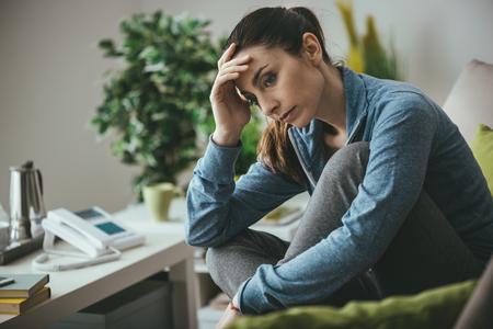 悲しい落ち込んで女性自宅のソファに座って、見下ろしていると彼女の額、孤独、痛みの概念に触れる