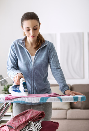 chores: Confident young woman at home ironing her clothes on the ironing board, housekeeping and chores concept Stock Photo