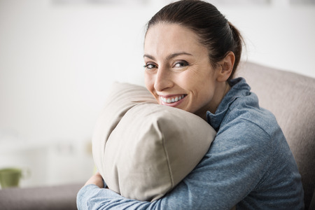 young woman smiling: Young woman at home sitting on the sofa and hugging a pillow, she is smiling at camera