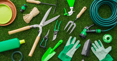 Gardening tools and utensils on a lush green meadow, top view, garden manteinance, landscaping and hobby concept