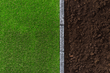 humus soil: Fertile humus soil and lush grass divided by a stone edging, gardening and landscaping concept