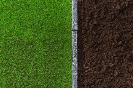 Vruchtbare humus bodem en weelderige gras gescheiden door een stenen rand, tuinieren en landschapsarchitectuur begrip Stockfoto