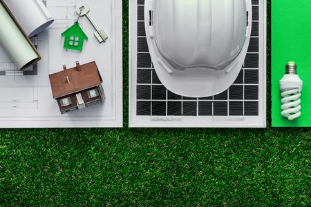 La construcción sostenible verde y el concepto de ahorro de energía: proyecto de la casa, paneles solares y herramientas de trabajo en la hierba, vista desde arriba