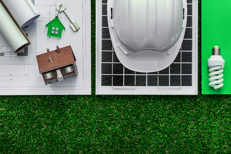 Sustainable green building and energy saving concept: house project, solar panel and work tools on the grass, top view
