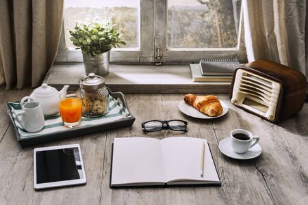 open country: Relaxing healthy breakfast at home: tray, coffee, vintage radio, tablet and a blank open notebook