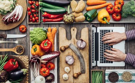 男はオンラインのレシピを探して新鮮な収穫野菜、調理器具、素朴なキッチンワークにノート パソコン、 写真素材