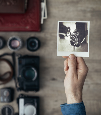 vintage photo: Photographic equipment, cameras and photo albums on a vintage desktop, a photographer is holding an instant photo Stock Photo