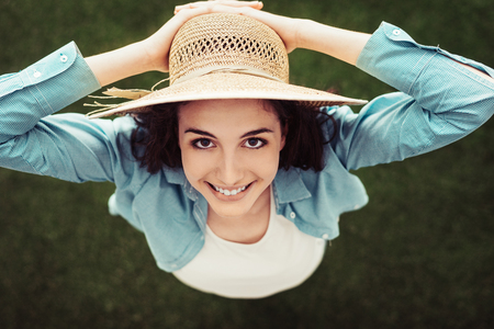 view woman: Smiling woman standing outdoors in nature and holding her straw hat, she is smiling at camera, top view