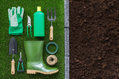 Gardening tools and utensils on the grass and fertile humus soil, farming and horticulture concept Stock Photo