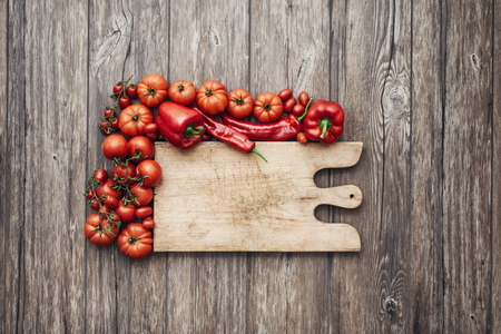 rustic kitchen: Red vegetables and rustic chopping board, healthy eating and cooking concept Stock Photo