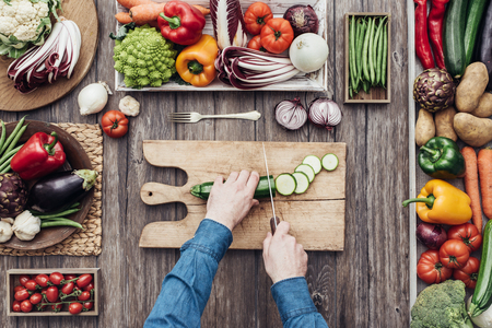 Man koken en snijden van verse groenten op een rustieke aanrecht, gezond eten concept, plat
