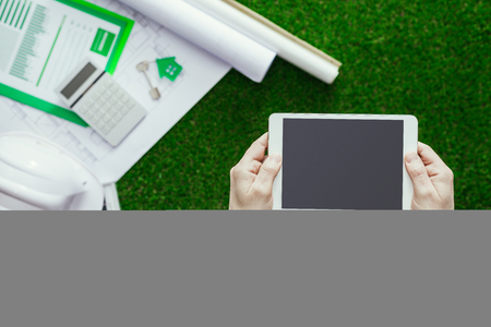 building safety: House project, solar panel, safety helmet on lush grass and male hands holding a tablet, green sustainable building and alternative energies concept
