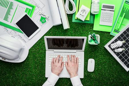 Eco house projecten, uitrustingsstukken en zonnepaneel op het gras, ingenieur werken met een laptop in het midden, groen bouwen en energiebesparing begrip