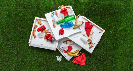 leftovers: Trash on the grass after a picnic outdoors: pizza boxes, cans, bottle and food leftovers