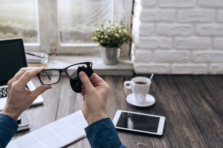 Man cleaning: Man sitting at desk at home and cleaning his glasses with a cloth
