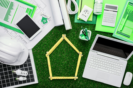 House project, tools, laptop and solar panel on a grass desktop, folding meter composing a house at center, green building concept Stock Photo