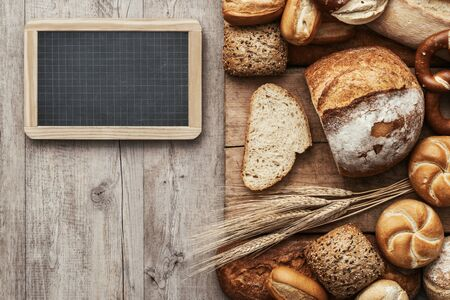 starchy food: Fresh crisp bread on a wooden worktop and blank chalkboard, bakery and healthy eating concept, flat lay banner