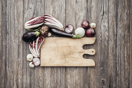 worktop: Purple and white vegetables on the kitchen worktop with rustic chopping board, healthy eating concept Stock Photo