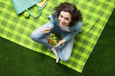 view girl: Smiling woman having a relaxing lunch break outdoors, she is sitting on the grass and eating a salad bowl
