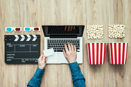 Man holding a ticket and watching a film streaming online with popcorn, 3D glasses and clapboard, movies and cinema concept Banco de Imagens