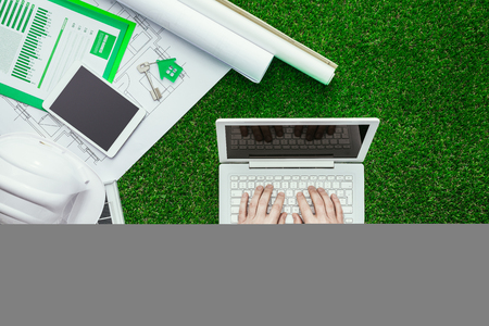 building safety: House project, solar panel, safety helmet and engineer working with a laptop on the grass, green sustainable building and alternative energies concept Stock Photo