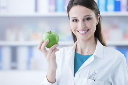 Vrouwelijke tandarts glimlachend en met een groene appel, tandheelkundige zorg en preventie-concept