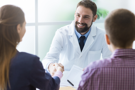 doctors smiling: Couple in the doctors office, the doctor is smiling and shaking the womans hand Stock Photo