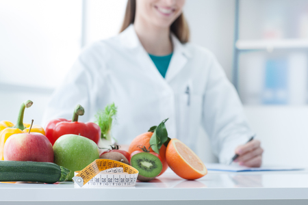 Nutritionist desk with healthy fruit, vegetables and a measuring tape, weight loss and diet concept