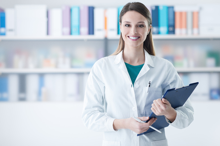 Smiling young female doctor holding a clipboard, healthcare concept