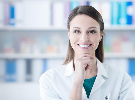 Het zekere het glimlachen vrouwelijke arts stellen in het bureau, gezondheidszorgconcept Stockfoto