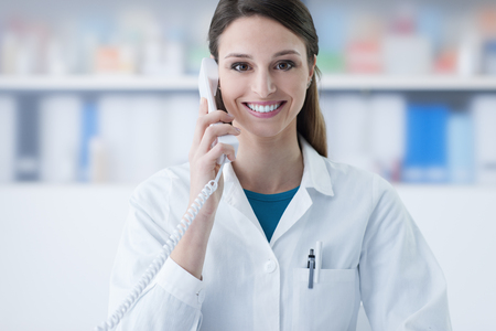 answering phone: Smiling female doctor holding a receiver and answering phone calls, medical service