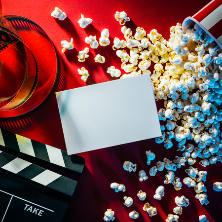 entertainment concept: Blank cinema promo card or ticket, popcorn, filmstrip and clapper, movies and entertainment concept