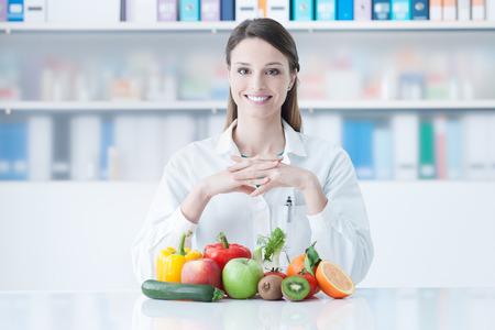 若い栄養士の机に座って、カラフルな野菜とフルーツ、健康的な食事、食事の概念を示す笑みを浮かべてください。