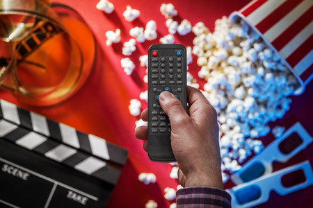 Hand holding a television remote control, popcorn, filmstrip, 3D glasses and clapper on the background, cinema and entertainment concept