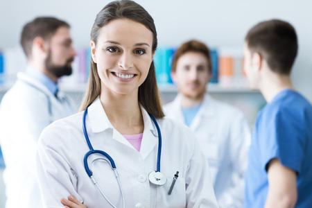 카메라를보고 청진 여성 의사 웃고, 배경에 의료 직원, 선택적 포커스 스톡 콘텐츠
