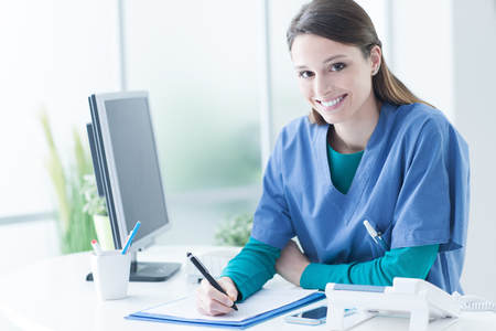 Yoing female doctor and practitioner working at the reception desk and writing medical reports Stock Photo - 59327314