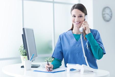 Jonge vrouwelijke arts en beoefenaar werken bij de receptie, is ze beantwoorden van telefoontjes en plannen van afspraken