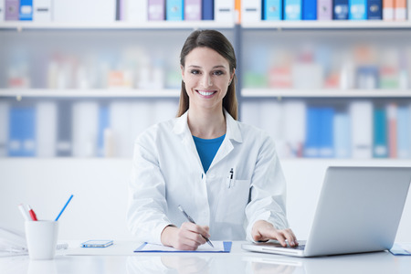 Young smiling female doctor sitting at office desk and working with a laptop Stock Photo