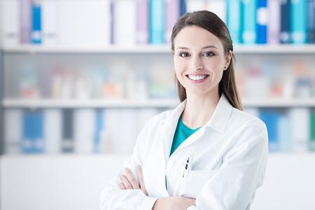 Zekere glimlachende vrouwelijke arts poseren in het kantoor, gezondheidszorg concept