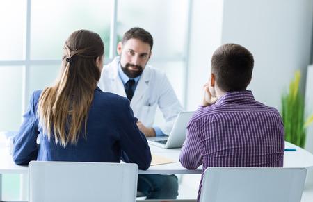 consulta médica: joven pareja en la consulta del médico durante una visita, el consejo médico y el concepto de la consulta