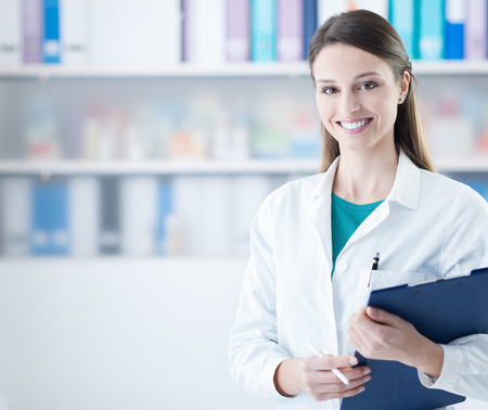 Smiling young female doctor holding a clipboard, healthcare concept Banco de Imagens - 59327322