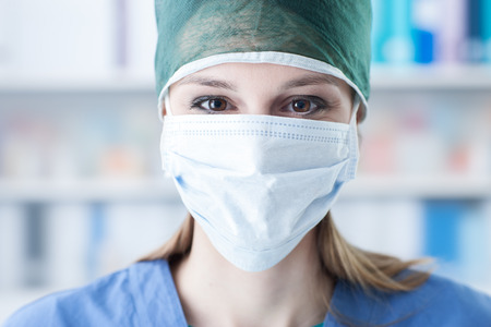 surgical mask: Female surgeon with cap and surgical mask, healthcare and medical procedures concept Stock Photo