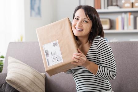 Lachende jonge vrouw thuis op de bank, heeft ze een postpakket, online winkelen en levering begrip ontvangen