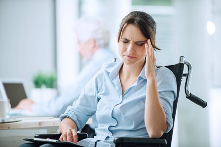 Disabled business woman in wheelchair at office having an headache touching her temples Stock Photo