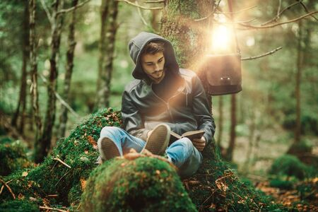 Man reading in nature and relaxing outdoors, freedom and individuality concept Stock Photo