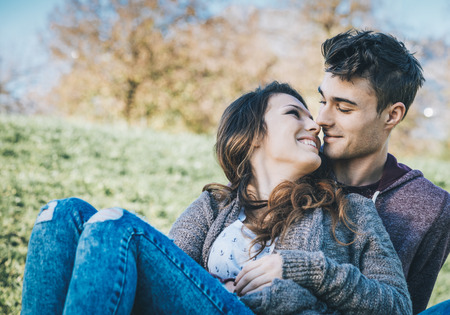 people relaxing: Happy young couple sitting on the grass, hugging and kissing outdoors, love and romance concept