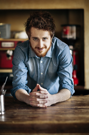 Young barman leaning on wooden bar counter and smiling at camera