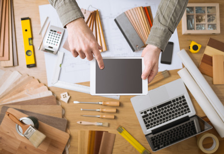 architect tools: Professional interior designer and architect hands close up holding and touching a digital tablet, work table with tools, wood swatches and laptop on background, top view