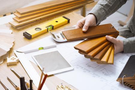 ベースボードと幅木、木製のスウォッチを保持しているプロのインテリア デザイナーのデスクで働きながらすぐ手します。
